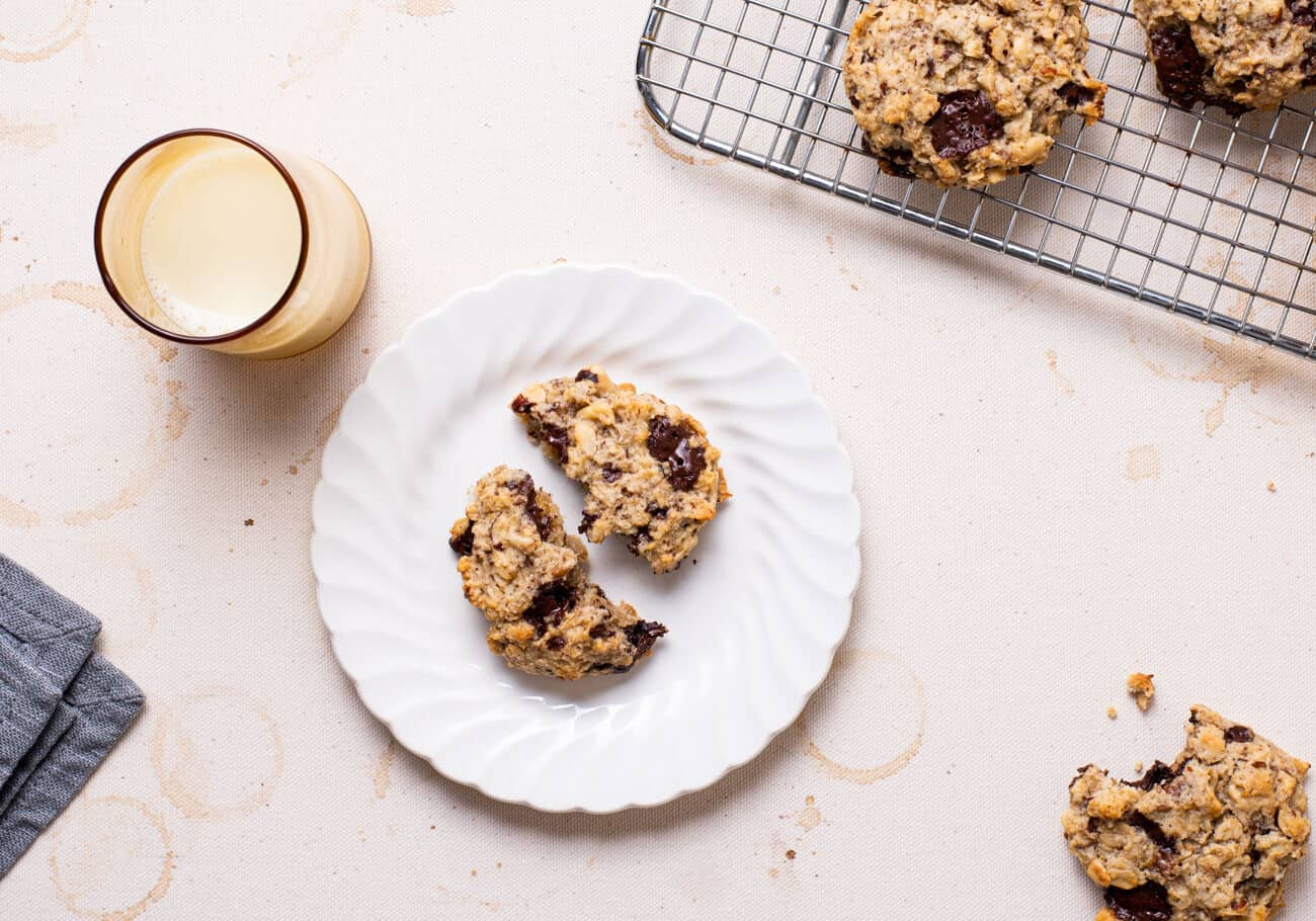 Banana oatmeal breakfast cookies on a cooling rack, and on white plates, next to a glass of milk.