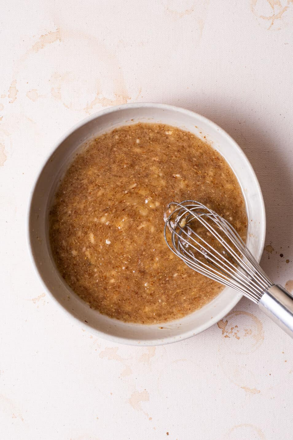 Mashed banana, coconut oil, and sugar whisked together in a bowl.