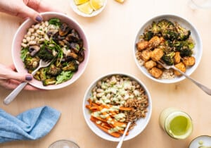 Ingredients gathered on a wooden table for vegan meal prep: tahini, chopped vegetables, farro, white beans, and herbs.